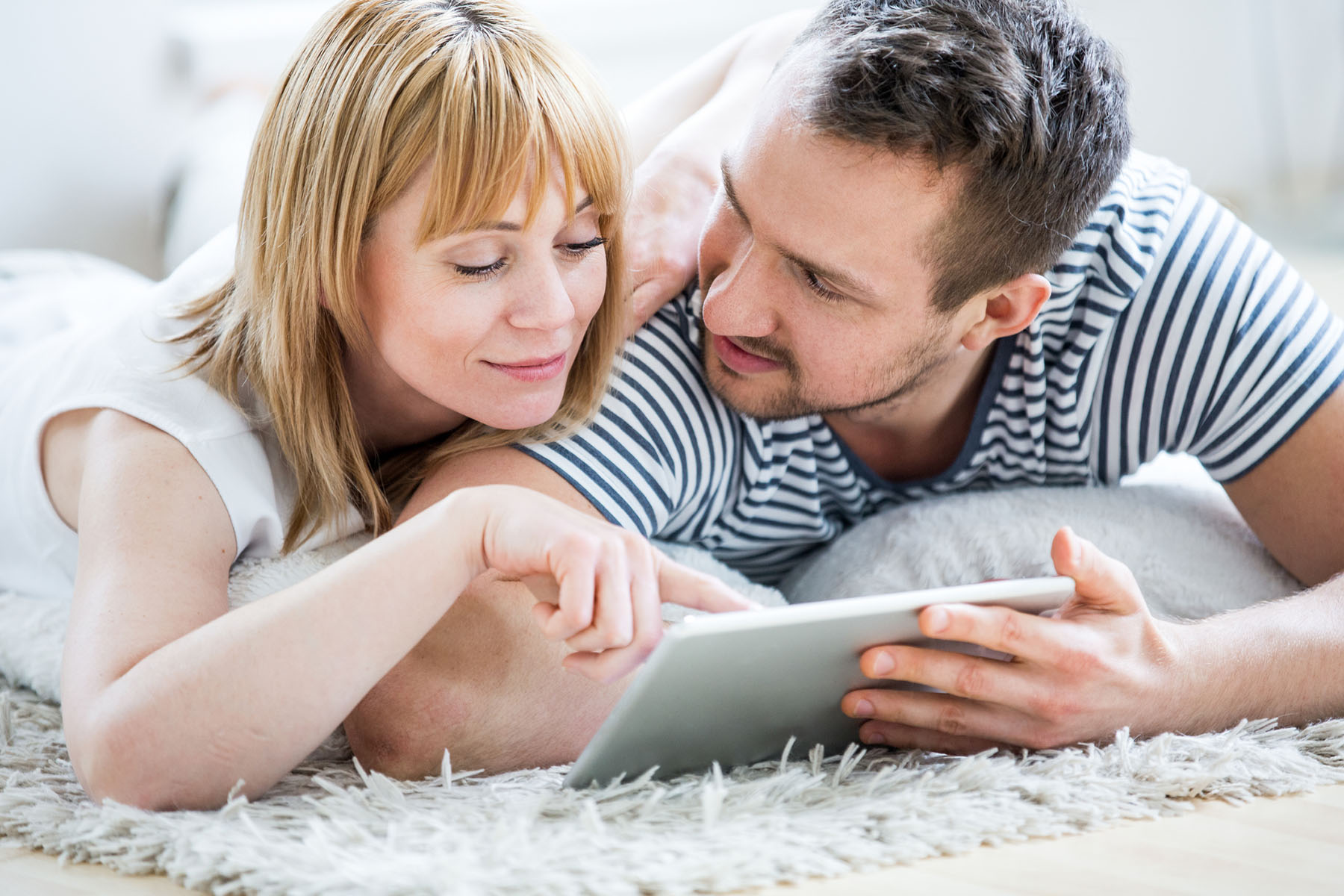 Couple with tablet lying on carpet